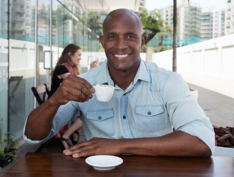 Afrikansk man som tycker om en kopp kaffe i en restaurang royaltyfria bilder
