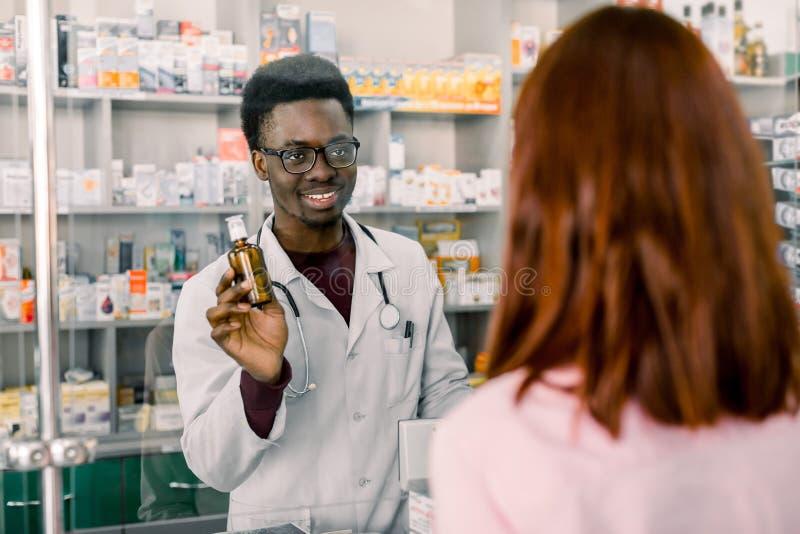 Afrikansk manapotekare och kvinnaklient på apotek arkivbild