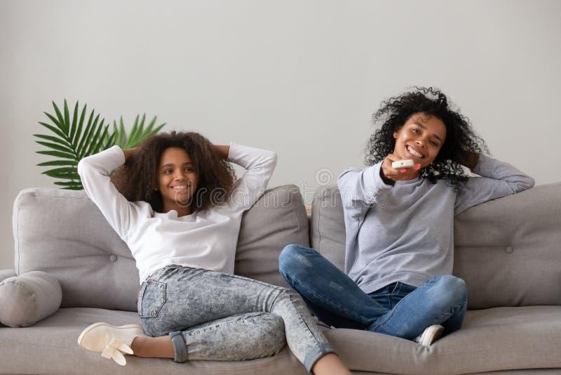 Afrikansk moder som rymmer fjärrkontroll som vilar med dottern på soffan arkivfoto