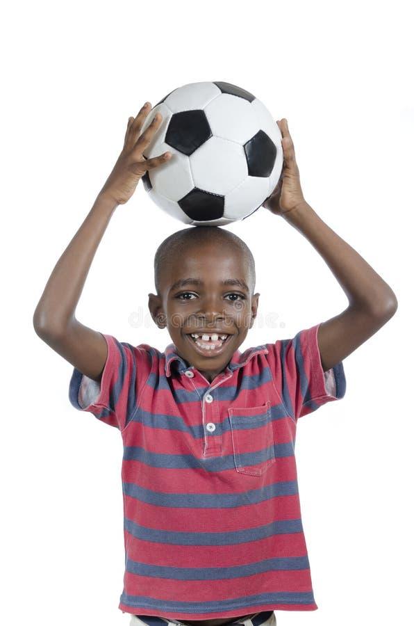 Afrikansk pojke med att le för fotboll arkivbild