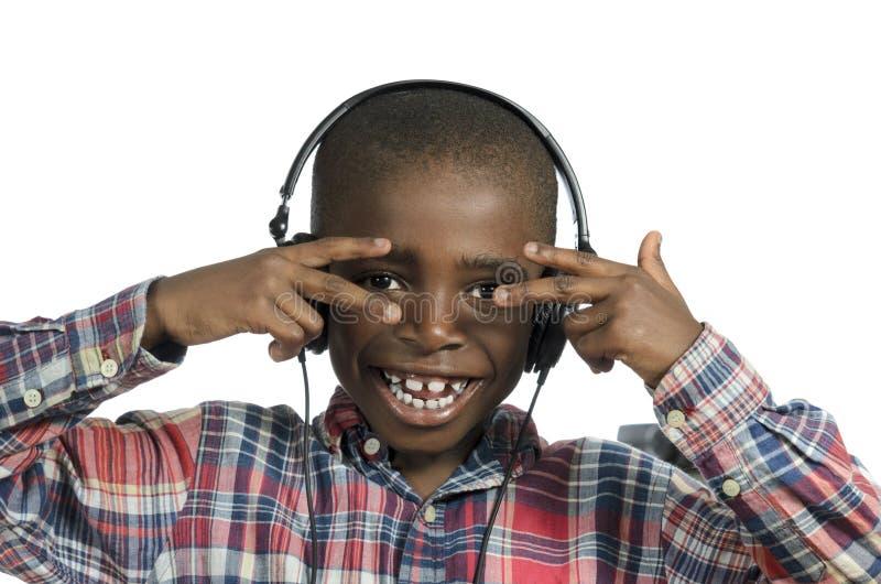 Afrikansk pojke med hörlurar som lyssnar till musik arkivbild