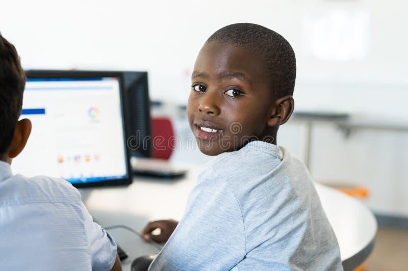 Afrikansk pojke som använder datoren på skolan arkivbild