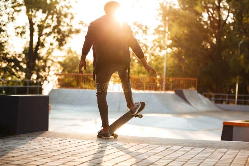 Afrikansk skateboarder som åker skridskor på en konkret skateboarding ramp royaltyfria bilder