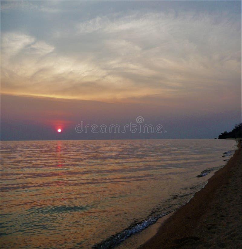 Afrikansk solnedgång i Mocambique över sjön med stranden royaltyfri foto