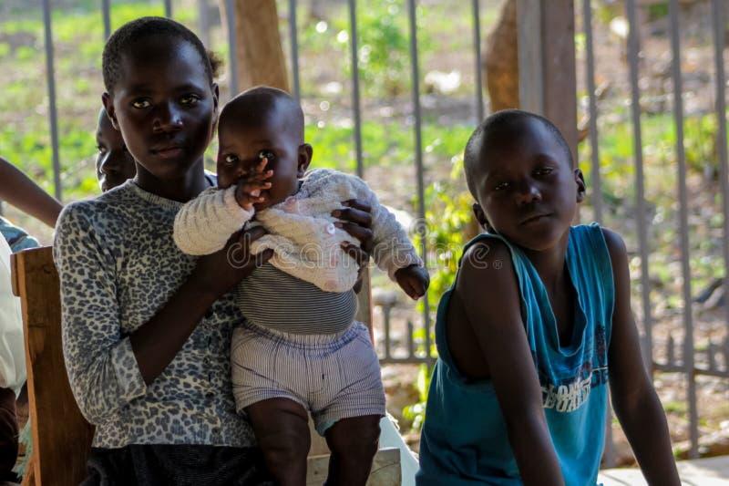 Afrikansk stående för litet barn, afrikansk pojke och flicka med en behandla som ett barn arkivbild