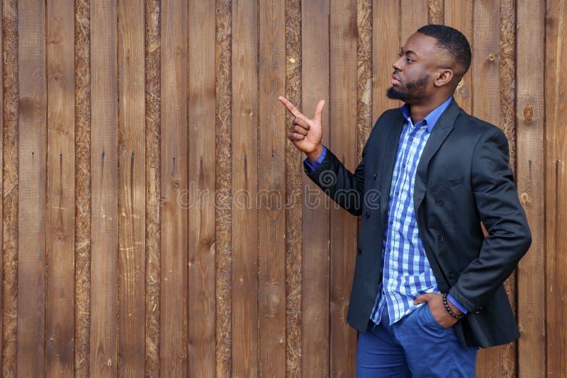 Afrikansk svart man med skägget som pekar den bort sidan med fingret på träbakgrund arkivbilder