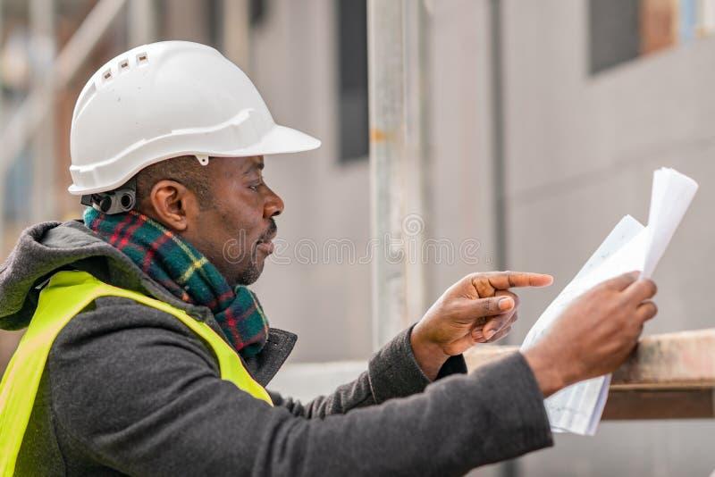 Afrikansk tekniker som kontrollerar kontorsritningar på konstruktionsplats royaltyfri foto