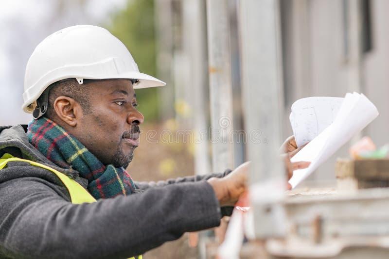 Afrikansk tekniker som kontrollerar kontorsritningar på konstruktionsplats royaltyfri bild