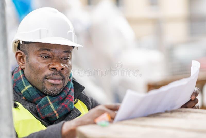 Afrikansk tekniker som kontrollerar kontorsritningar på konstruktionsplats fotografering för bildbyråer