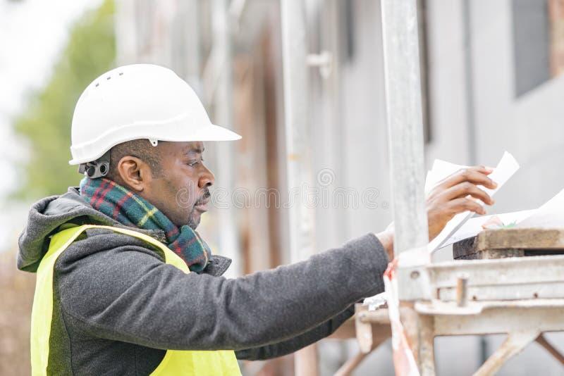 Afrikansk tekniker som kontrollerar kontorsritningar på konstruktionsplats arkivfoto