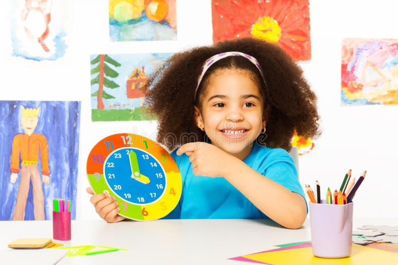 Afrikansk tid för klocka för flickainnehavlåda royaltyfri foto