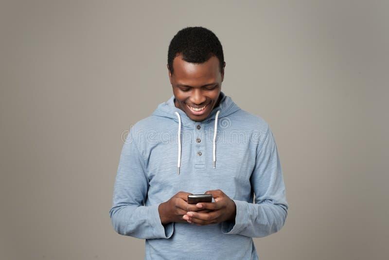 Afrikansk ung man som använder mobiltelefonen som pratar i internet med hennes vänner royaltyfria bilder