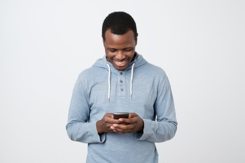 Afrikansk ung man som använder mobiltelefonen som pratar i internet med hennes vänner royaltyfri foto