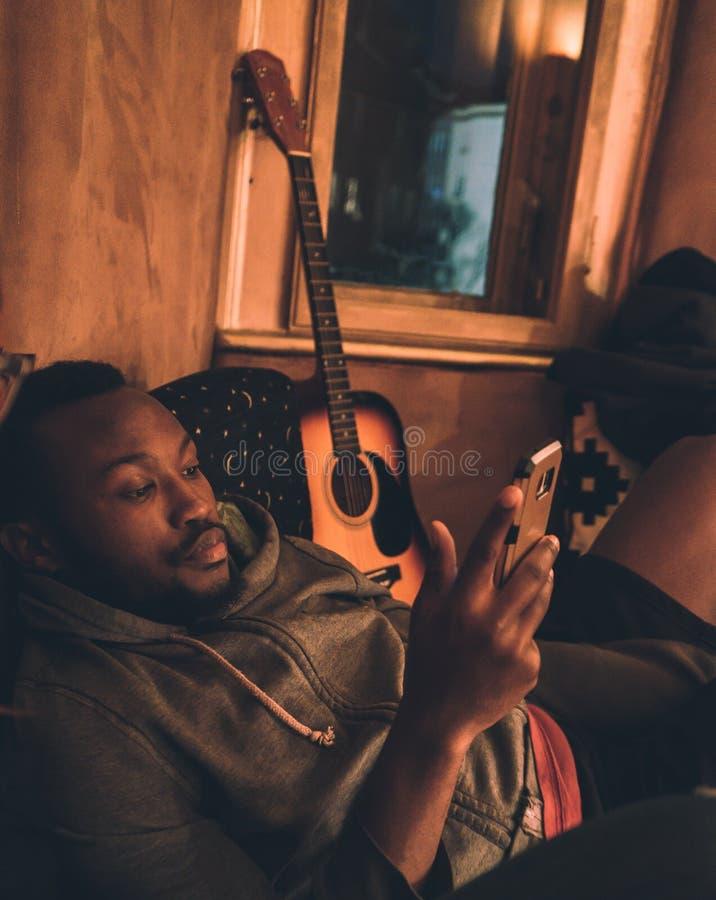 Afrikansk ung svart grabb med skägget genom att använda smartphonen som lägger ner i en lagledare och en gitarr arkivfoton
