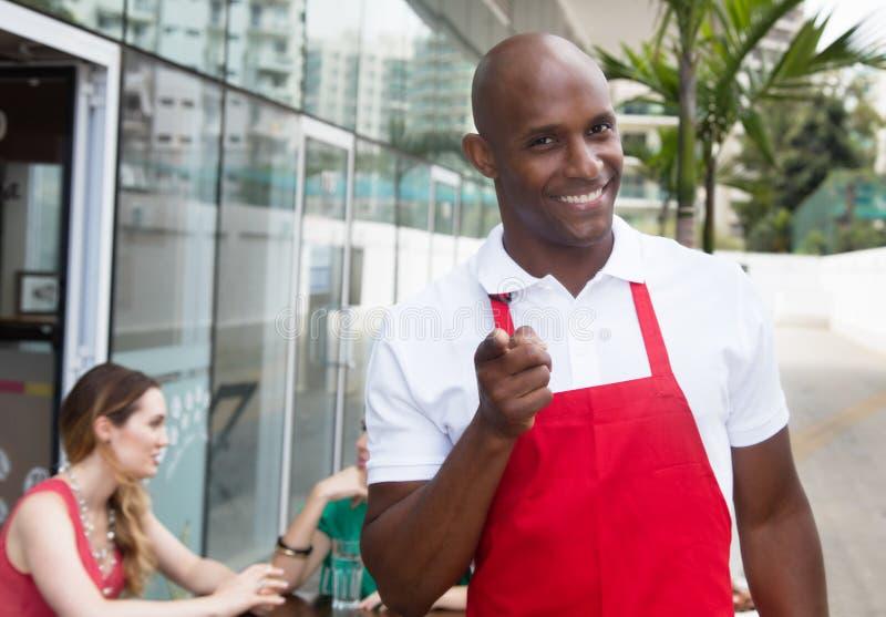 Afrikansk uppassare på arbete i en restaurang som pekar på kameran med gäster royaltyfria foton