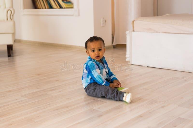 Afrikanska amerikanen behandla som ett barn pojken inomhus fotografering för bildbyråer