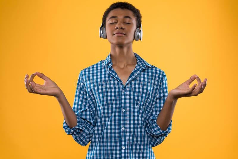 Afrikanska amerikanen som är tonårig i hörlurar, mediterar royaltyfria foton