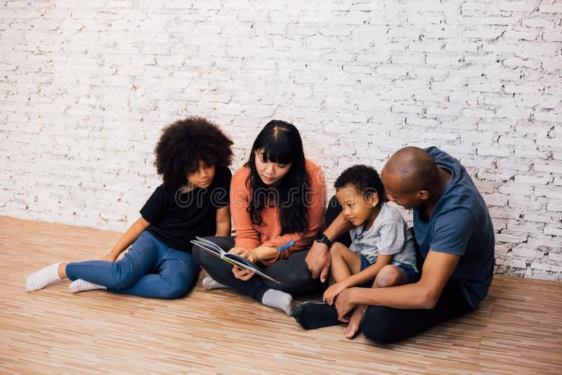 Afrikanska amerikanen uppfostrar att läsa en sagafabelberättelse för ungar hemma Lyckligt familjsammanträde på golvet inomhus arkivbilder
