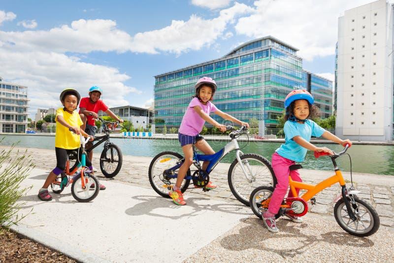 Afrikanska barn som tycker om att cykla tillsammans i stad royaltyfri fotografi