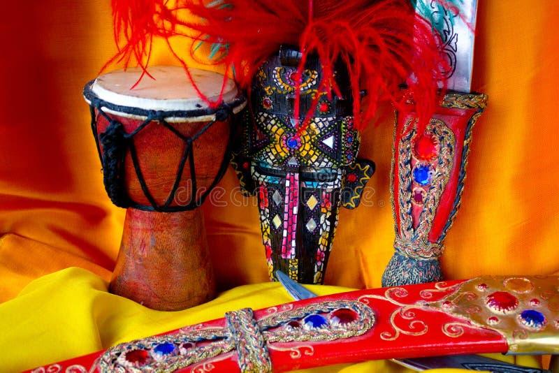 Afrikanska brädspelobjekt på gul och orange bakgrund royaltyfria bilder