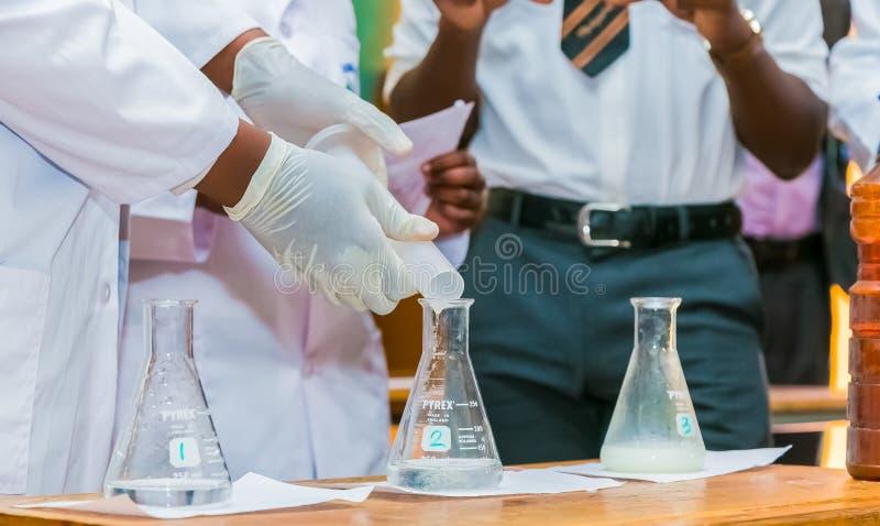 Afrikanska grundskola för barn mellan 5 och 11 årstudenter som gör en vetenskapsdemonstration arkivfoton