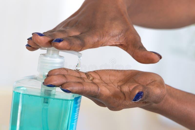 Afrikanska kvinnas för Hygiens begrepp händer genom att använda handsanitizeren arkivbilder