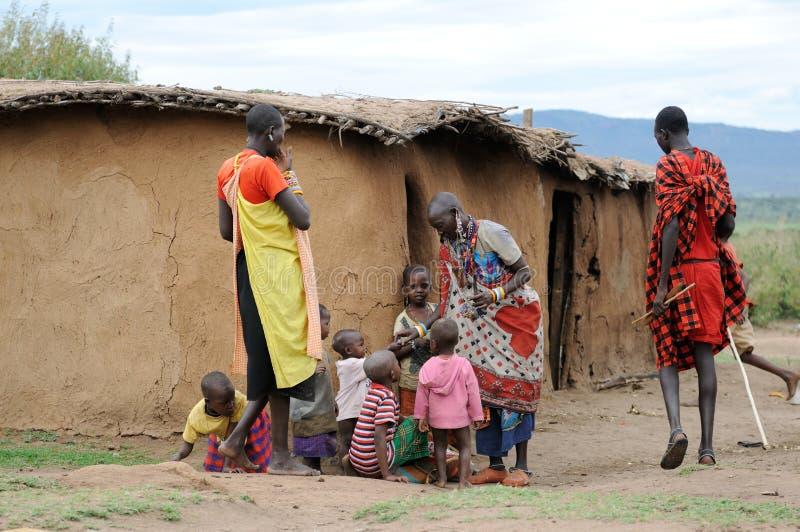 Afrikanska kvinnor ger ett armband till henne barn arkivbild