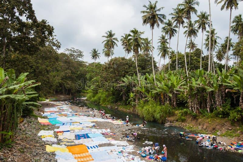 Afrikanska kvinnor som tvättar kläder på en flod i Sao Tome arkivbilder