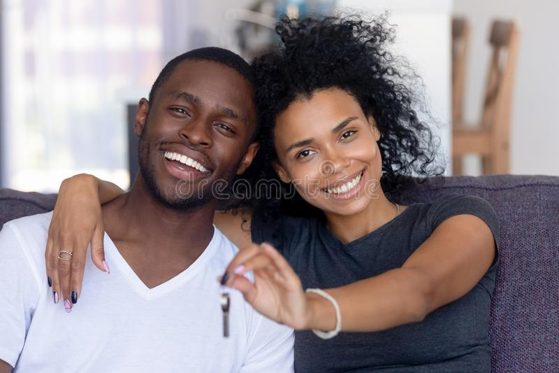 Afrikanska par som sitter på soffan som rymmer tangenter från nytt hus royaltyfria foton