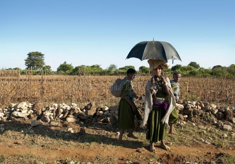 Afrikanska stamflickor som går längs vägen i ethiopia arkivbild
