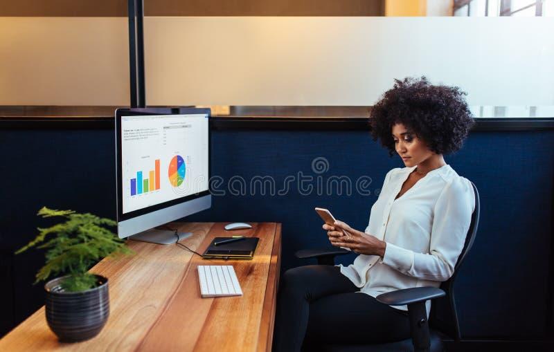 Afrikanskt affärskvinnasammanträde på hennes skrivbord genom att använda mobiltelefonen royaltyfria bilder