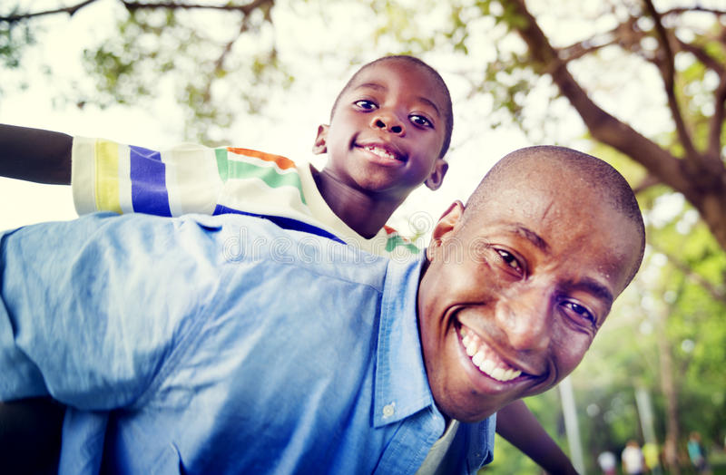 Afrikanskt för sonfarsa på ryggen för familj begrepp utomhus royaltyfria foton