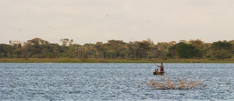 Afrikanskt folk som korsar en sjö i dugoutkanot arkivbilder