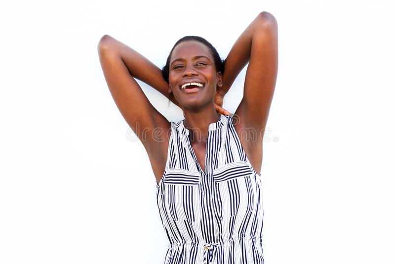Afrikanskt kvinnaanseende med händer bak huvudet och skratta på vit bakgrund arkivfoton