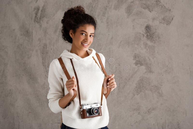 Afrikanskt kvinnligt le för fotografi som rymmer kameran över beige bakgrund arkivbild