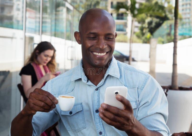 Afrikanskt manhälerimeddelande på telefonen i en restaurang royaltyfri bild
