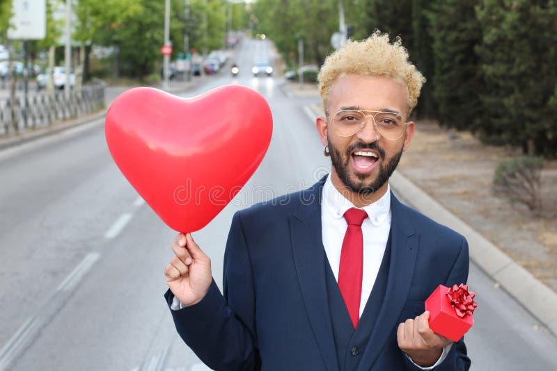 Afro- affärsman som rymmer hjärtaballon- och gåvaasken royaltyfri fotografi