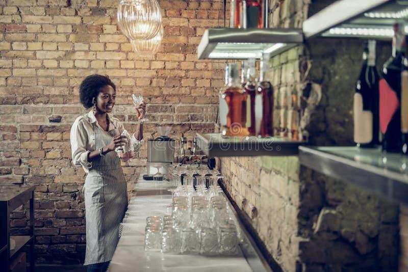 Afro-Américain mince de prétraitement vérifiant la propreté en verre à la barre photos stock
