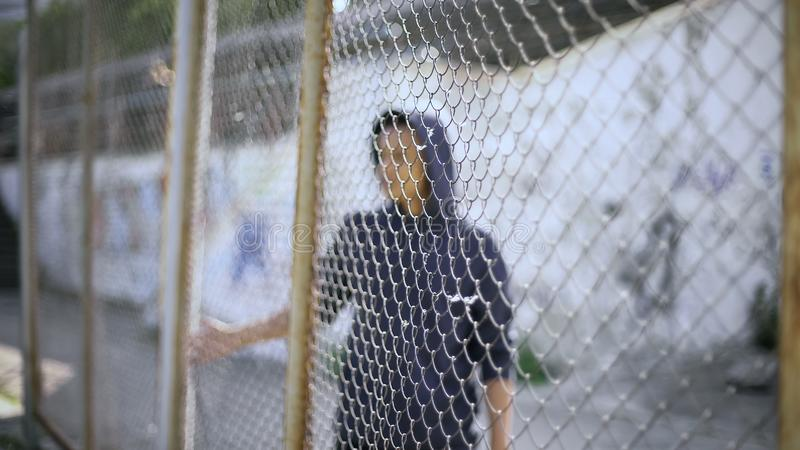 Afro-american boy behind fence, migrant child separated from family, detained. Stock photo stock image