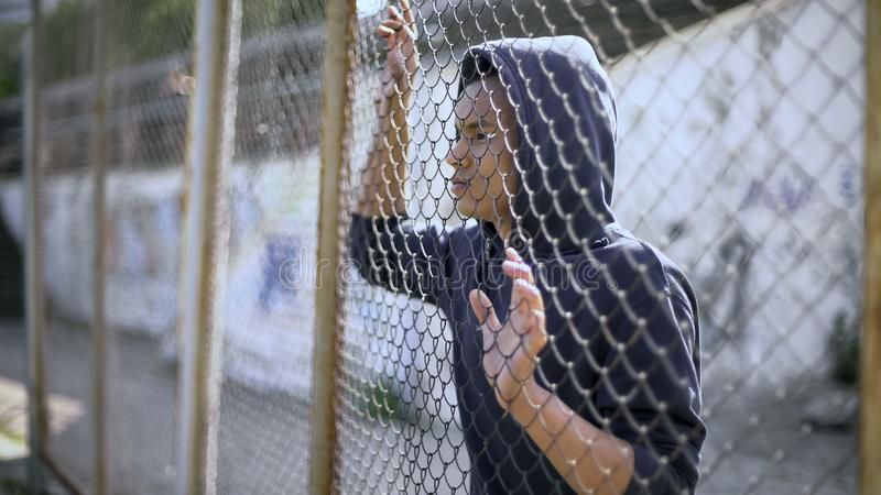Afro-american boy behind metal fence, criminal in prison, dreaming about freedom. Stock photo royalty free stock image