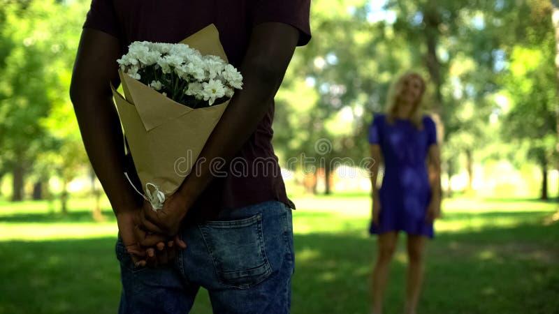 Afro-american boyfriend hiding flowers bouquet behind back in park, surprise stock image