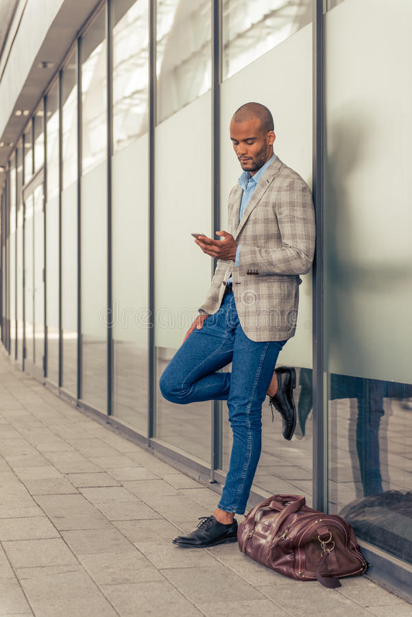 Afro American businessman with gadget. Full length portrait of handsome stylish young Afro American businessman using smartphone, standing outdoors near his stock images
