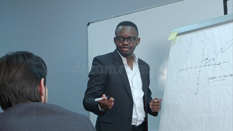 Afro-american businessman making presentation of a business plan on the flipchart. Close up. Professional shot in 4K resolution. 085. You can use it e.g. in royalty free stock images