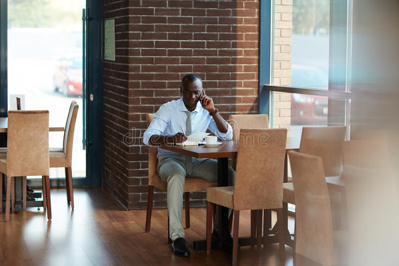 Afro-American Businessman Working at Cafe. Full length portrait of concentrated African American entrepreneur talking to his business partner on mobile phone and royalty free stock photo