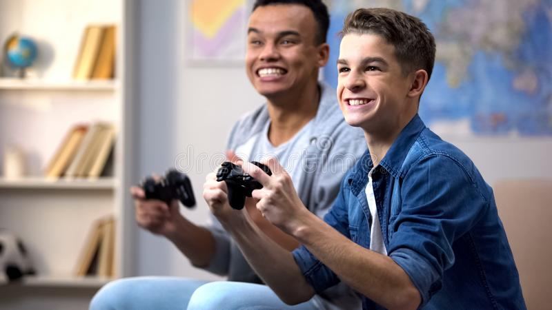 Afro-american and caucasian boys happy to win video game leisure time activity. Stock photo royalty free stock photos