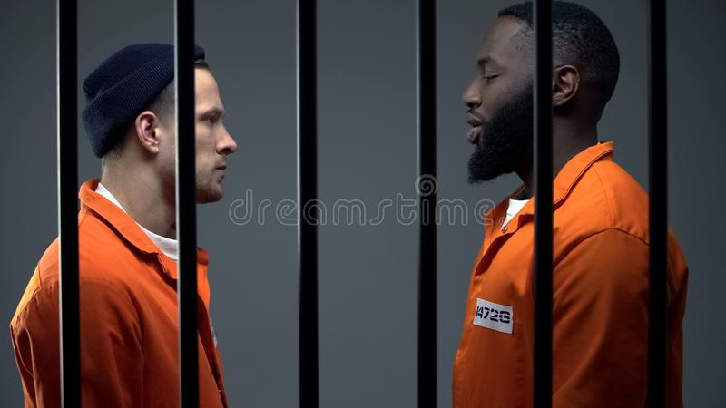 Afro-american and caucasian inmates looking at each other in cell, conflict royalty free stock photo