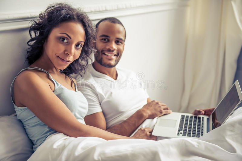 Afro American couple. Beautiful young Afro American couple is using a laptop, looking at camera and smiling while lying in bed at home stock image