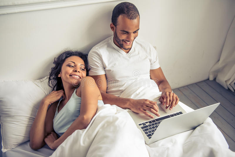 Afro American couple. Beautiful young Afro American couple is using a laptop and smiling while lying in bed at home royalty free stock images