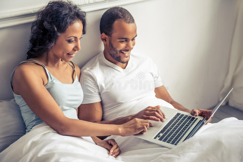 Afro American couple. Beautiful young Afro American couple is using a laptop and smiling while lying in bed at home royalty free stock photo