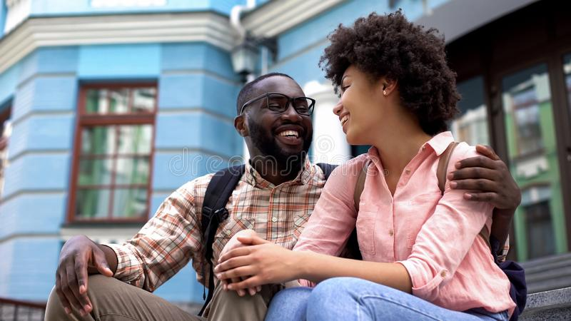 Afro-american couple having fun together, sitting stairs, urban date outdoor royalty free stock photo